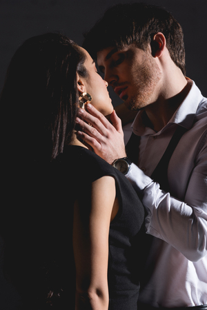 man in white shirt and woman in black dress kissing on black background