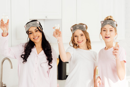 beautiful multicultural girls in sleeping masks celebrating with champagne and looking at camera during pajama party