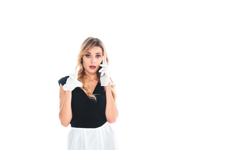 blonde housemaid in black uniform talking on smartphone isolated on white Stock Photo