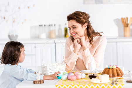 Mother and child sitting at table with easter cake and painted eggs and looking at each other