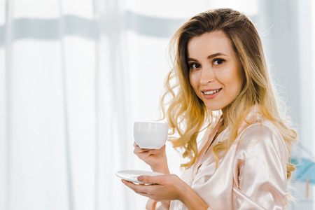 Blissful blonde woman in pyjamas drinking coffee in morning