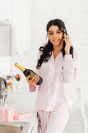 beautiful smiling african american girl holding bottle of champagne while talking on smartphone