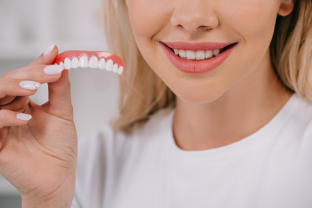 cropped view of smiling woman holding teeth cover