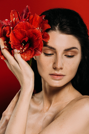 beautiful woman with freckles on face posing with amaryllis flowers, isolated on red Stock Photo