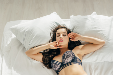 overhead view of beautiful brunette woman in bra lying on bed with closed eyes