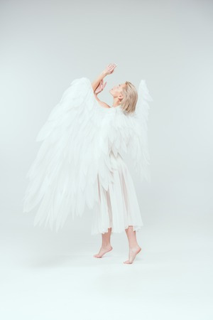 beautiful tender woman with angel wings gesturing with hands and posing on white background Stock Photo