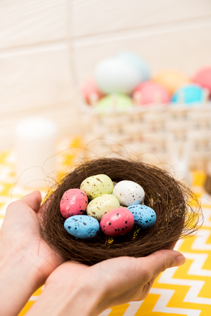 Partial view of woman holding nest with painted easter eggs