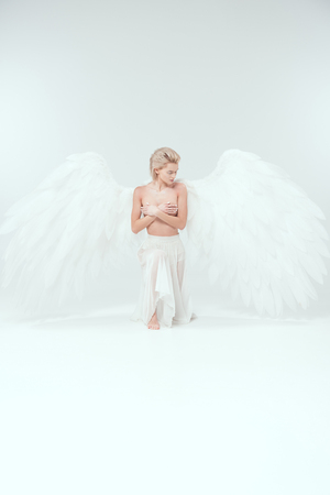 beautiful young woman with angel wings covering breasts while posing on white background Stock Photo