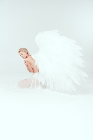 beautiful woman with angel wings sitting with eyes closed on isolated on white