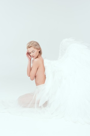 beautiful woman with angel wings sitting with eyes closed isolated on white Stock Photo