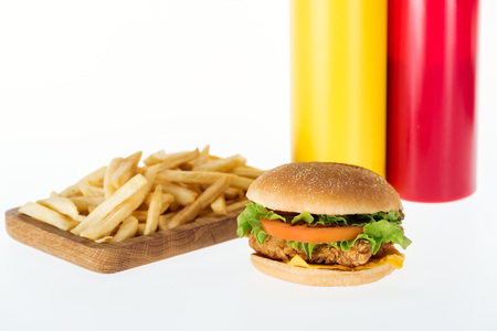 tasty chicken burger near french fries and bottles isolated on white Stock Photo
