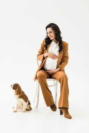 Brunette pregnant woman sitting on chair and looking at dog on white background Stock Photo