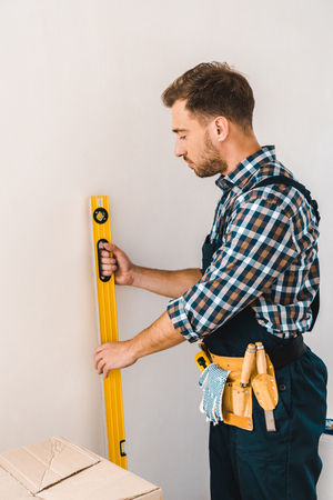 handsome handyman holding measuring level near wall