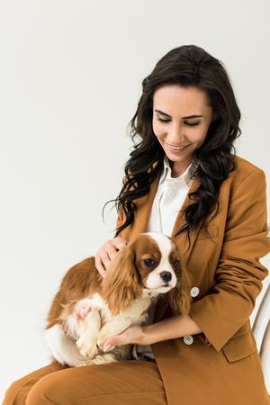 Attractive curly woman in brown jacket holding dog isolated on white