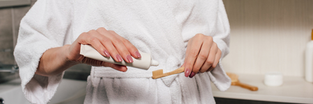 panoramic shot of woman applying toothpaste on toothbrush in bathroom Stock Photo
