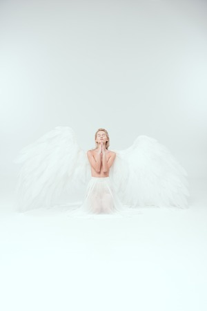 beautiful woman with angel wings praying isolated on white with copy space Stock Photo