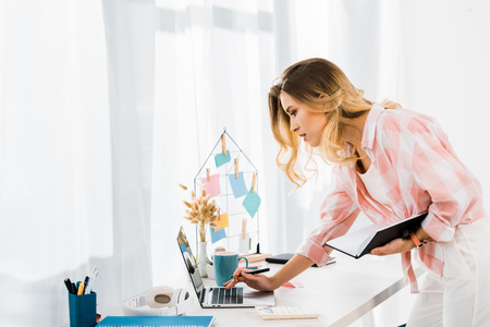 Concentrated young woman with notebook using laptop at home office