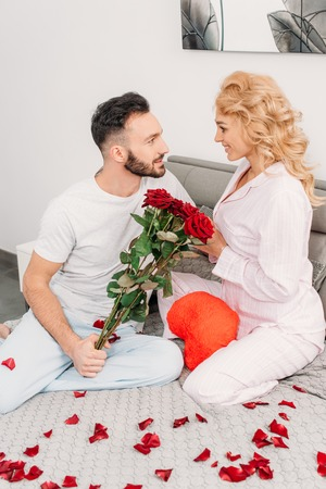 Blissful couple sitting on bed with roses and toy heart