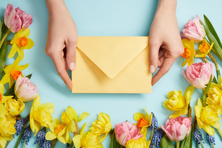 partial view of female hands with yellow envelope, pink tulips, yellow daffodils and blue hyacinths on blue