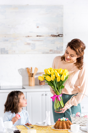Child eating macaroon and looking at mother with tulips bouquet in kitchen