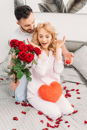 Brunette man presenting flowers and ring box to surprised girlfriend in bedroom