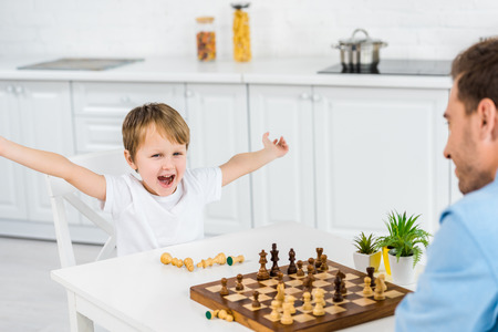 preschooler son cheering with hands in air while playing chess with father at home