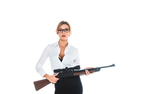 teacher in blous with open neckline, glasses and skirt holding rifle isolated on white