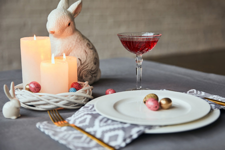 selective focus of plates with napkin, eggs and burning candles in basket, wine in crystal glass and decorative rabbit on table at home
