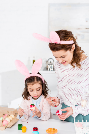 Cheerful mother and daughter in bunny ears painting easter eggs in kitchen Banco de Imagens