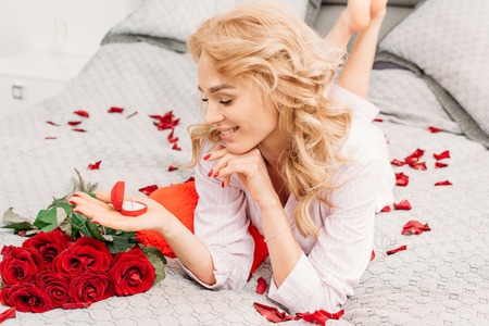 Happy blonde girl lying on bed with flowers and holding ring Stock Photo