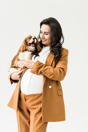 Smiling pretty pregnant woman holding dog isolated on white Stock Photo
