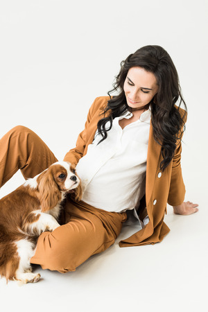 Charming pregnant woman sitting on floor and looking at dog on white background Stock Photo