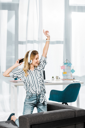 Blissful girl in striped shirt with smartphone dancing and listening music in headphones
