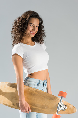 Shapely curly girl holding longboard isolated on grey