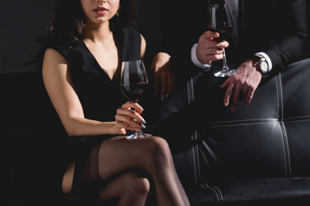 cropped view of woman sitting in dress wile handsome man in black suit standing behind couch and holding glass with wine on black background