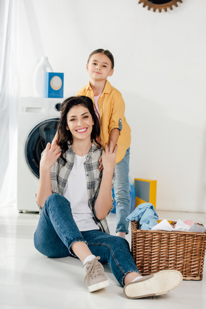 daughter in yellow shirt holding mother sitting on floor near basket in laundry room 写真素材