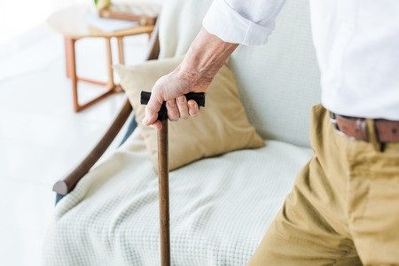 cropped view of senior man holding walking cane near sofa 스톡 콘텐츠
