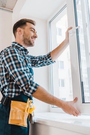 cheerful handyman with tool belt smiling while opening window