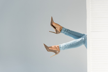 Cropped view of woman in jeans and brown high-heeled shoes on grey background