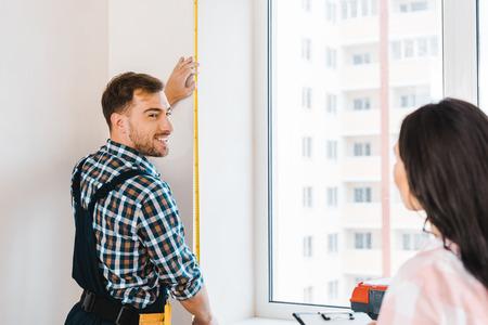 selective focus of cheerful handyman measuring window near female client 写真素材