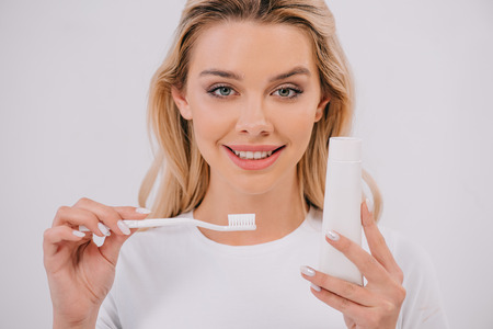 beautiful woman looking at camera while holding toothbrush and toothpaste with copy space isolated on white