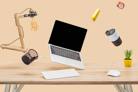 laptop with blank screen and stationery levitating in air at workplace isolated on beige