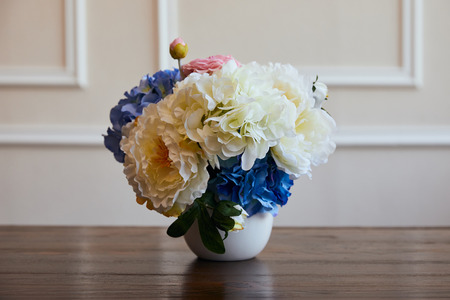 hydrangea and piones in white vase on wooden table at home