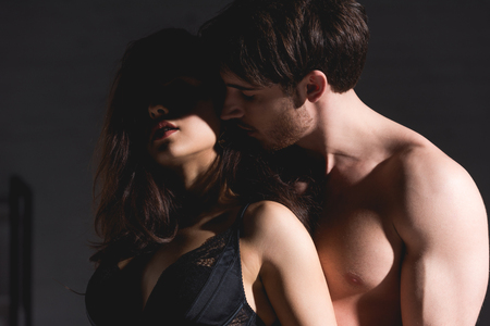 woman in black lingerie and shirtless man standing and hugging on black background