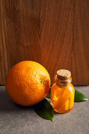 Whole orange with glass bottle of essential oil on dark surface 스톡 콘텐츠
