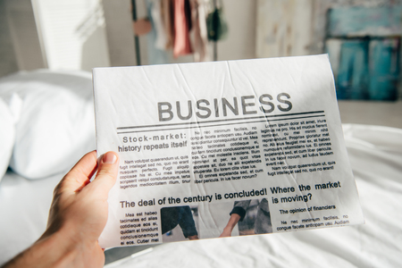 cropped view of man holding business newspaper