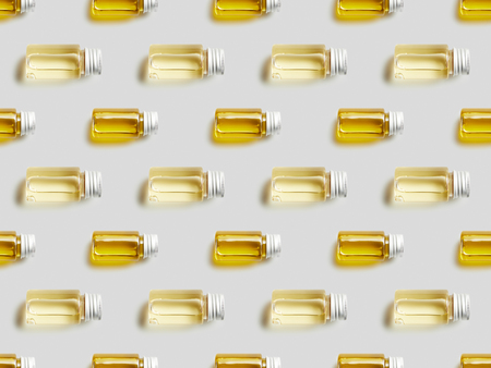 Top view of glass bottles with essential oil on grey background