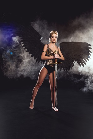 beautiful woman in warrior costume with angel wings holding sword and posing on black background