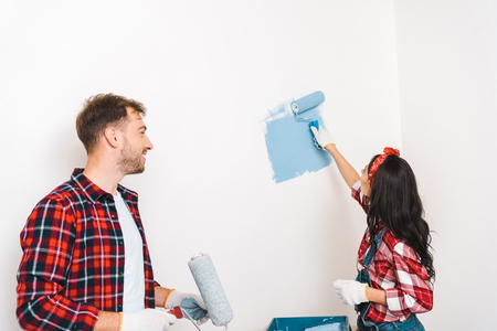 woman painting wall in blue color near cheerful boyfriend at home Standard-Bild - 119072779