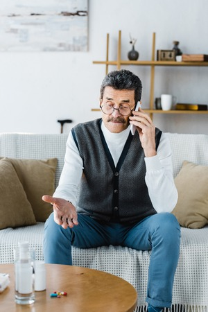 selective focus of senior man talking on smartphone near pills and glass of water
